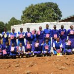 The Water Project: St. Teresa's Isanjiro Girls Secondary School -  Students At The Tank Construction Site With Training Booklets