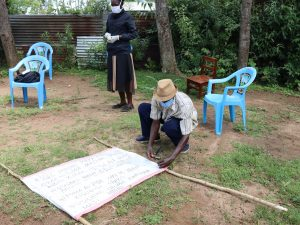 The Water Project:  A Coomunity Member Helping Nail The Chart To The Support Poles