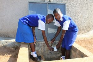 The Water Project:  Students Collecting Water At The Completed Water Tank