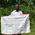 The Water Project: Lwenya Community, Warosi Spring -  A Participant Holding Up The Reminder Chart