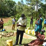 The Water Project: Lwenya Community, Warosi Spring -  Trainer Alulu Leading The Handwashing Exercise
