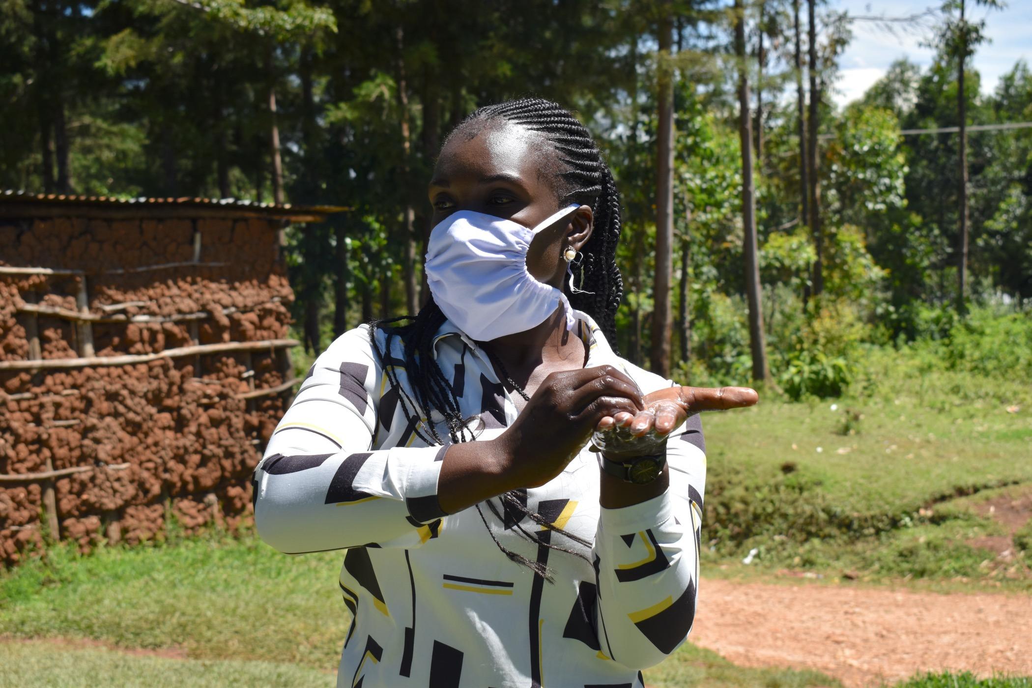 The Water Project : 6-covid19-kenya18136-miss-alulu-demonstrating-handwashing