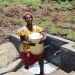 The Water Project: Mahira Community, Jairus Mwera Spring -  Mounting Full Jerrycan On Head