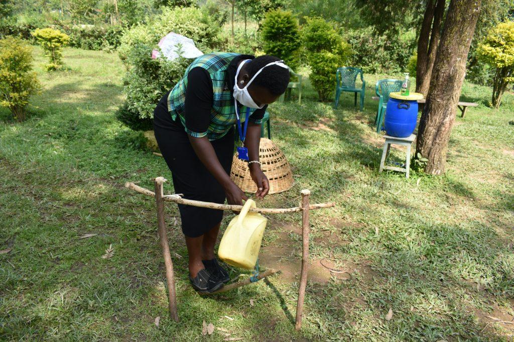 The Water Project : covid19-kenya18100-ms-karen-erecting-a-simple-handwashing-station
