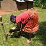 The Water Project: Musango Community, Ham Mwenje Spring -  Community Member Using A Simple Handwashing Station
