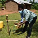 The Water Project: Musango Community, Ham Mwenje Spring -  Facilitator Shows Participants How To Use Tippy Tap