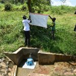 The Water Project: Mungaha B Community, Maria Spring -  Sir Victor Being Helped By A Young Gent To Mount The Chart At The Spring