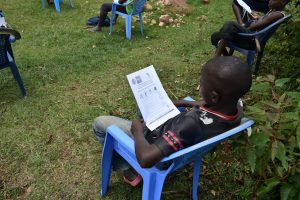 The Water Project:  A Boy Reading Through The Pamphlet