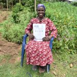The Water Project: Emaka Community, Ateka Spring -  A Community Member Smiling With Her Pamphlet