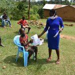 The Water Project: Emaka Community, Ateka Spring -  Mrs Afandi Issuing Training Pamphlets