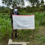 The Water Project: Emaka Community, Ateka Spring -  The Facilitator Standing Next To The Chart At The Spring
