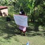 The Water Project: Koloch Community, Solomon Pendi Spring -  Facilitator Holds Up Sack With Covid Cautions At The Training