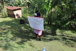 The Water Project:  Facilitator Holds Up Sack With Covid Cautions At The Training