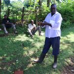 The Water Project: Samisbei Community, Isaac Rutoh Spring -  An Elder Practices Handwashing In Front Of Participants
