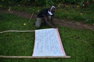 The Water Project:  Mr Wagaka Mounting The Chart To The Support Poles
