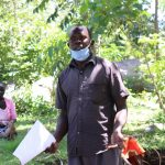 The Water Project: Imbinga Community, Arunga Spring -  A Community Health Volunteer Showcasing Wrong Ways Of Wearing Masks