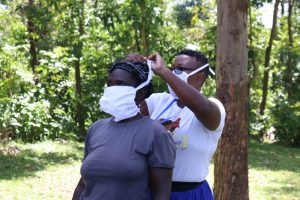 The Water Project:  Jacky Demonstrates By Helping A Community Member Tie Her Mask Properly