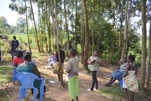 The Water Project:  Community Members Listening In To Ms Shigali