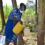 The Water Project: Maondo Community, Ambundo Spring -  Ms Shigali Filling The Handwashing Station With Water