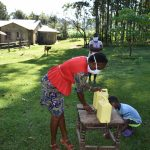 The Water Project: Malimali Community, Shamala Spring -  Demonstration On How To Use A Leaky Tin