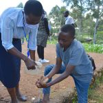 The Water Project: Lutonyi Community, Lutomia Spring -  Ms Serete Helping A Young Man Rinse His Hands Using Running Water