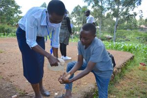 The Water Project:  Ms Serete Helping A Young Man Rinse His Hands Using Running Water