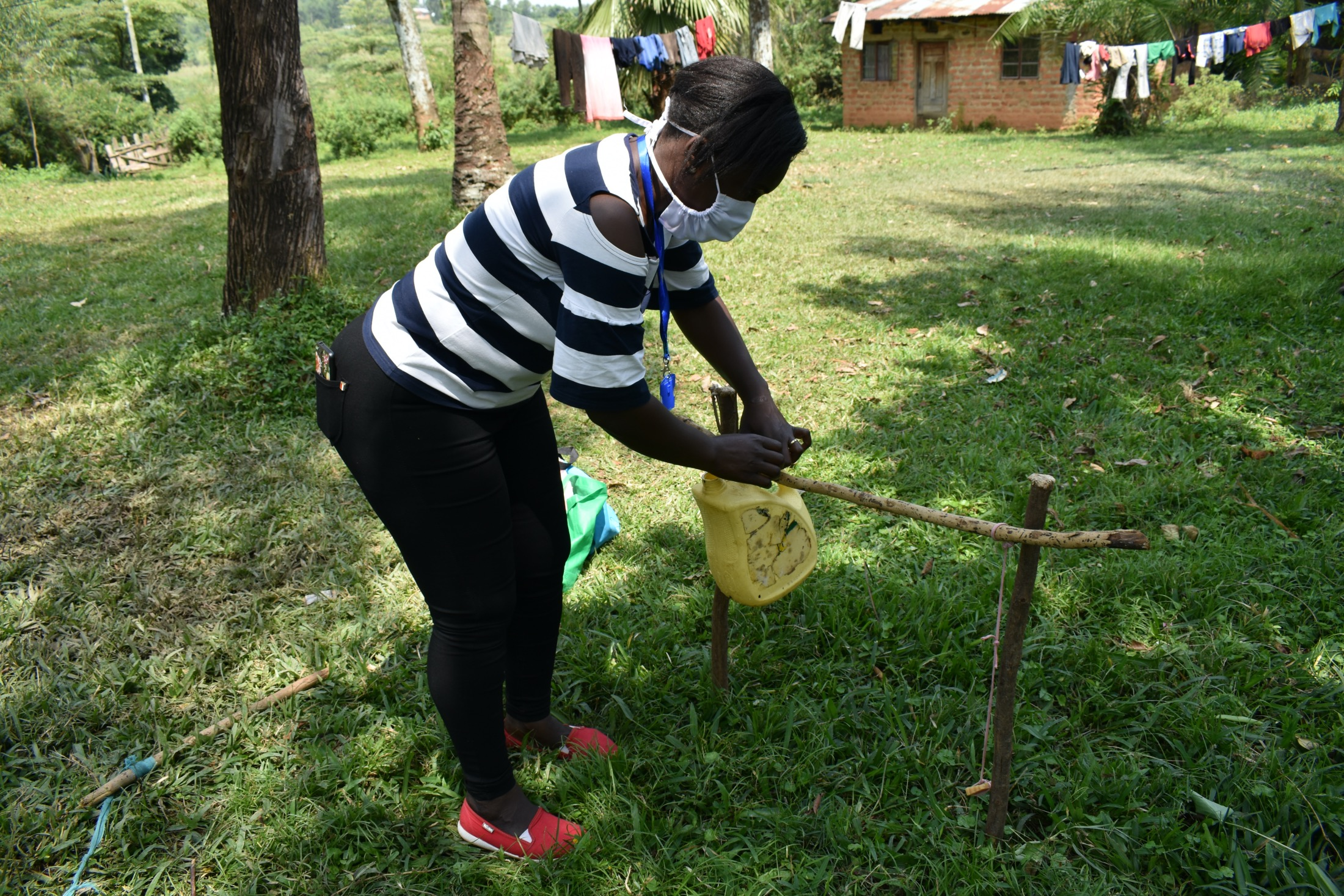 The Water Project : covid19-kenya4427-ms-laura-erecting-a-tippy-tap-handwashing-station