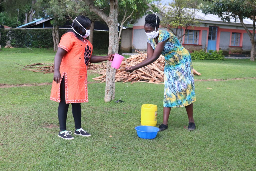 The Water Project : covid19-kenya4558-the-facilitators-demonstrating-how-to-clean-your-hands