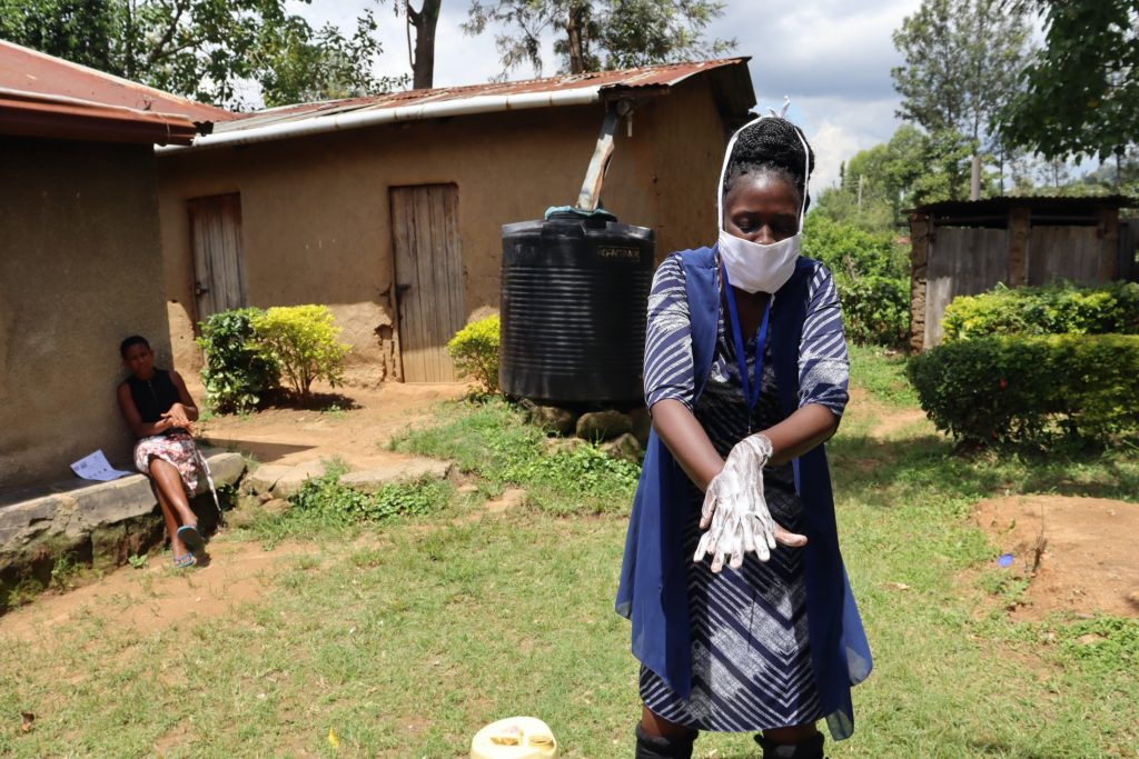 The Water Project : covid19-kenya4593-the-facilitator-leading-the-demonstration-of-the-ten-steps-of-handwashing
