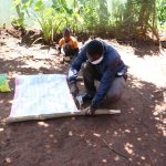 The Water Project: Mutambi Community, Kivumbi Spring -  Sir Samuel Simidi Nailing The Chart Onto The Support Poles