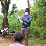 The Water Project: Mutambi Community, Kivumbi Spring -  The Facilitator Demonstrating How To Make A Mask