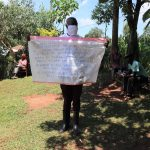 The Water Project: Mutambi Community, Kivumbi Spring -  The Facilitator Holding Up The Reminder Chart