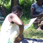 The Water Project: Eshiakhulo Community, Omar Sakwa Spring -  A Community Member Reading Through The Pamphlet