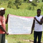 The Water Project: Futsi Fuvili Community, Shikanga Spring -  Two Community Members Holding Up The Chart