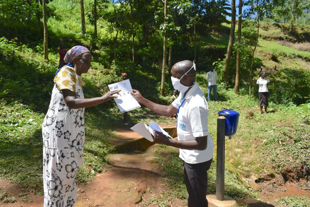 The Water Project : covid19-kenya4751-issuing-handouts-with-coronavirus-precautions-to-participants