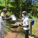 The Water Project: Elunyu Community, Saina Spring -  Issuing Handouts With Coronavirus Precautions To Participants