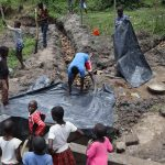 The Water Project: Mukhonje Community, Mausi Spring -  Polythene Tarp Backfilling