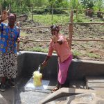 The Water Project: Mukhonje Community, Mausi Spring -  Community Member Collecting Water