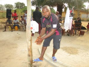 The Water Project:  Young Man Demonstrating Handwashing Method