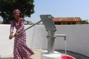The Water Project:  Woman Pumps The New Well