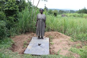 The Water Project:  A Woman Stands With Her Completed Sanplat