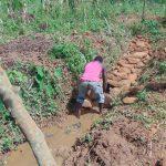 The Water Project: Ewamakhumbi Community, Mukungu Spring -  Backfilling With Stones