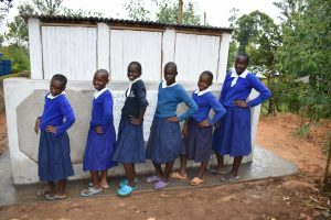 The Water Project:  Girls Posing In Front Of Their Latrines