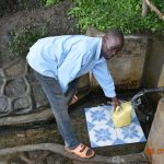 The Water Project: Munenga Community, Burudi Spring -  Silas Fetches Water From Burudi Spring