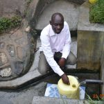 The Water Project: Emukoyani Community, Ombalasi Spring -  Niskson Fetches Water At Ombalasi Spring