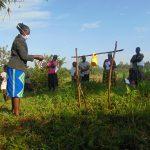 The Water Project: Shihingo Community, Mulambala Spring -  Community Members Closely Follow Mask Making