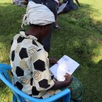 The Water Project: Musango Community, Dawi Spring -  A Lady Reading Through The Manual
