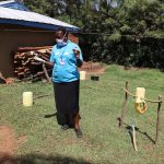 The Water Project: Mwituwa Community, Nanjira Spring -  Facilitator Directing How To Use A Handwashing Station