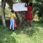 The Water Project: Muyundi Community, Baraza Spring -  The Facilitators Mounting The Chart At The Waterpoint