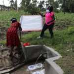 The Water Project: Muyundi Community, Ngalame Spring -  The Facilitators Mounting The Chart To The Poles